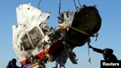 FILE - Local workers haul away a piece of wreckage of Malaysia Airlines flight MH17 at the site of the plane's crash near the village of Hrabove, Donetsk region, eastern Ukraine, Nov. 20, 2014.