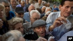 Para warga pensiunan Yunani antri di bank untuk menguangkan check pensiun mereka, Rabu (1/7).