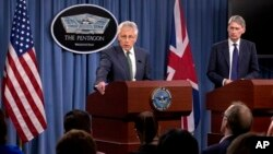 Defense Secretary Chuck Hagel, accompanied by British Defense Secretary Philip Hammond, addresses reporters following talks at the Pentagon, near Washington, May 2, 2013.