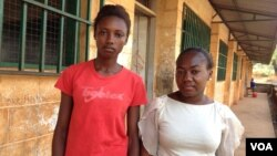Elizabeth Issa (left) stands with a fellow student outside a school offering classes for pregnant and lactating mothers in Freetown, Sierra Leone, Feb. 22, 2016. (Photo - Nina deVries/VOA)