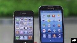 ໂທລະສັບ Galaxy S III (ຢູ່ທາງຂວາ) ຂອງບໍລິສັດ Samsung ແລະ iPhone 4S ຂອງ Apple are ວາງສະແດງ ຢູ່ຮ້ານຂາຍໂທລະສັບແຫ່ງນຶ່ງ ຢູ່ກຸງໂຊລ ຂອງເກົາຫລີໃຕ້ ໃນວັນທີ 24 ສິງຫາ, 2012.