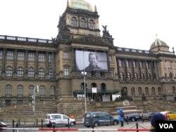 捷克国家博物馆悬挂着前总统哈维尔的大幅画像。捷克国家博物馆位于布拉格瓦茨拉夫广场顶端。当地是1968年布拉格之春和1989年天鹅绒革命的主要地点。布拉格之春被苏军镇压后,国家博物馆外墙上布满弹孔。