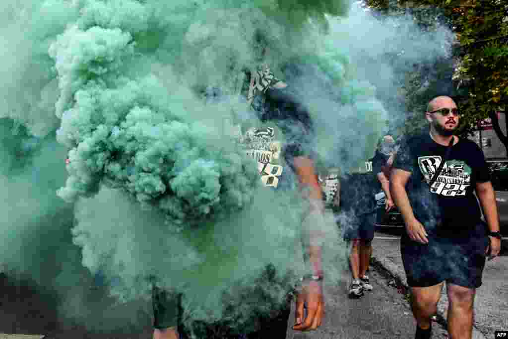 A man walks in flare smoke as he arrives with some fellow supporters of Hungarian football club Ferencvaros at the Maksimir Stadium in Zagreb, August 6, 2019, to attend the UEFA Champions League play off football match against Dinamo Zagreb, Croatia.