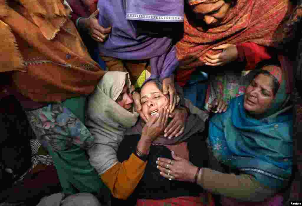 مظاہروں میں ہلاک ہونے والے پولیس اہلکار کی بیوہ کو خواتین دلاسہ دیتے ہوئے۔