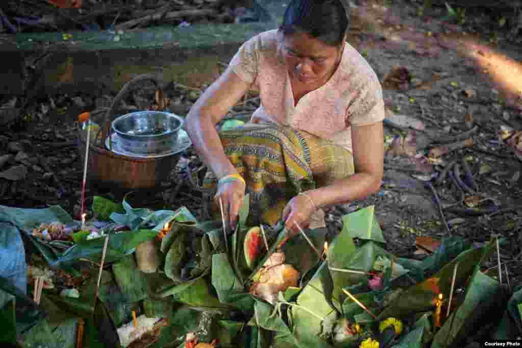 Lá chuối đựng thức ăn đem cúng được đặt dưới gốc cây trong lễ hội Boon Pradub Khao Din hàng năm ở đông bắc Thái Lan, ngày 24 tháng 8, 2014. Nghi lễ tỏ lòng tôn kính đối với đất đai và tinh hồn của những người thân đã qua đời. (Ảnh của Matthew Richards/ Thái Lan / độc giả VOA)