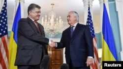 FILE - U.S. Secretary of State Rex Tillerson shakes hands with Ukrainian President Petro Poroshenko during their meeting at the U.S. State Department in Washington, June 20, 2017. Tillerson and a new special representative will visit Ukraine Sunday.