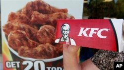 A customer holds a box of Kentucky Fried Chicken outside an KFC restaurant, Tuesday, July 13, 2010, in Mountain View, Calif. (AP Photo/Paul Sakuma)