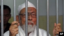 Indonesian militant cleric Abu Bakar Bashir - jailed for 15 years for his involvement with a group that aimed to kill the country's president - speaks to journalists while he waits inside a cell before his trial at South Jakarta court, June 16, 2011