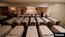 Seorang petugas memeriksa peti jenazah di rumah duka Gerard J. Neufeld di kawasan Queens, New York, AS, di tengah pandemi COVID-19, 26 April 2020. (REUTERS / Bryan R Smith)