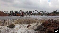 Warga setempat melewati jalanan yang rusak akibat banjir di wilayah Hyderabad, negara bagian Andhra Pradesh di selatan India (26/10).