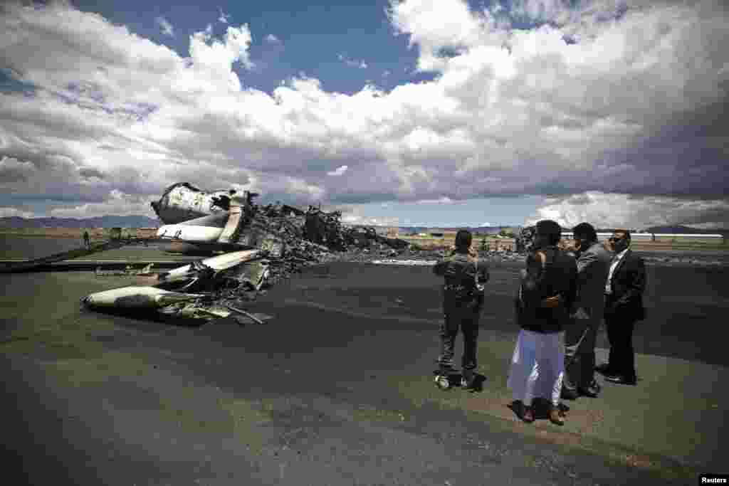 Airport officials look at the wreckage of a military transport aircraft destroyed by Saudi-led airstrikes, at the Sanaa International Airport, in Yemen. A Saudi-led coalition continues to bomb Shiite rebels known as Houthis and allied forces across the country.