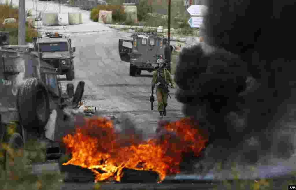 Một thành viên của lực lượng an ninh Israel đi đằng sau những lốp xe bốc cháy trong những vụ đụng độ với người biểu tình Palestine ở lối vào thị trấn Al-Bireh của người Palestine ở ngoại ô thành phố Ramallah, ở vùng Bờ Tây do Israel chiếm đóng.
