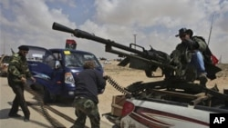 A Libyan rebel, dressed as a cowboy, mans an anti-aircraft gun as fellow rebels load ammunition as they wait for the signal to advance at an intersection just outside Brega, Libya, Sunday, April 3, 2011. Libyan rebels want to install a parliamentary demo