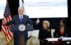 Mike Pence speaks at education meeting, as Educaton Secretary Betsy DeVos (center) watches.