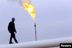 FILE - A worker walks on an oil pipeline at Khurmala oil field on the outskirts of the city of Arbil, in Iraq's Kurdistan region, Dec. 4, 2013.