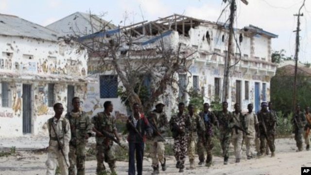 Somali government soldiers patrol after fighting against Islamist insurgents al Shabaab in Suqa Holaha village of Horiwaa district, northern Mogadishu, March 3, 2012.
