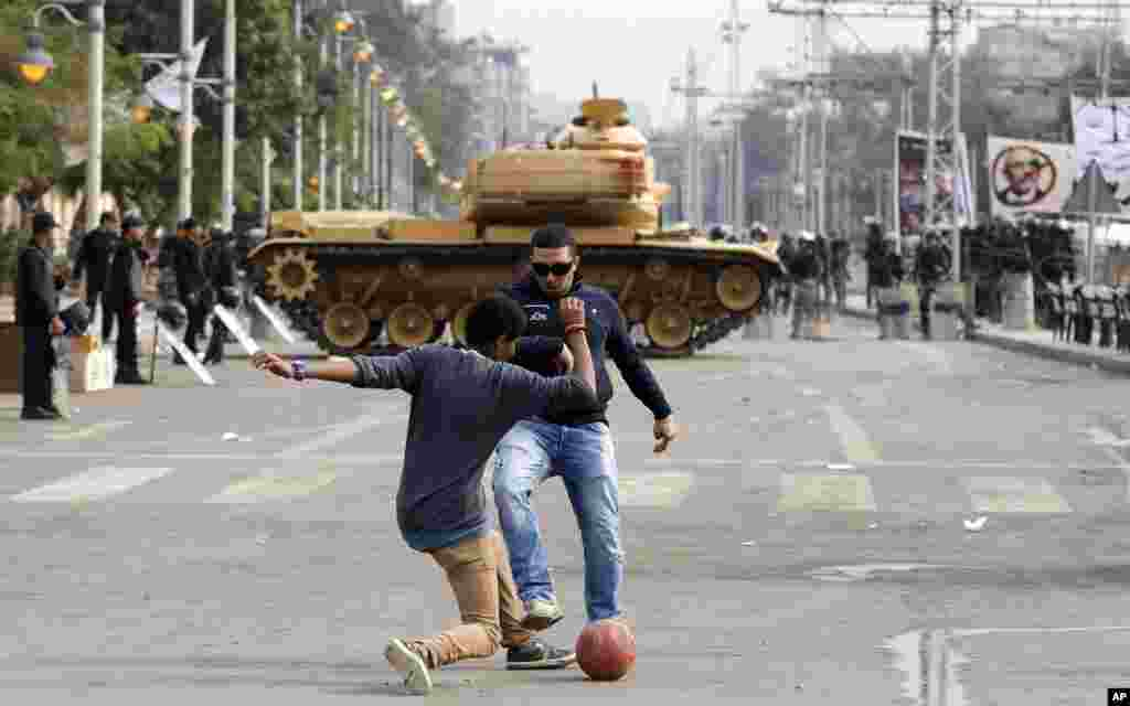 Protesters play with a ball in front of a tank securing the area around the presidential palace in Cairo, Egypt, Dec. 14, 2012.