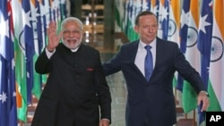India's Prime Minister Narendra Modi, left, escorted by Australian Prime Minister Tony Abbott, waves as they leave the House of Representatives at Parliament House in Canberra, Tuesday, Nov. 18, 2014.