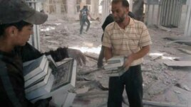 Residents of Qusair, Syria salvage copies of the Quran from a mosque bombed by government forces on May 21, 2013.  Members of the militant Shi'a Hezbollah in Lebanon have joined regime troops to retake the border town of Qusair from rebel hands.