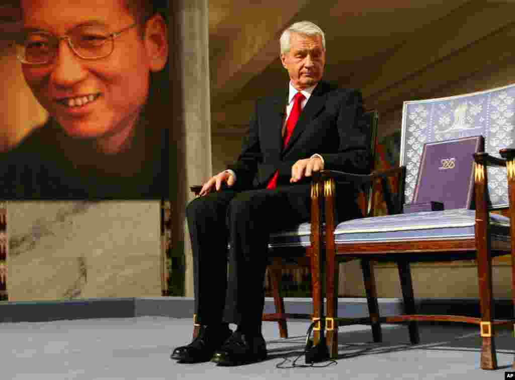 Chairman of the Norwegian Nobel Committee Thorbjoern Jagland looks down at the Nobel certificate and medal on the empty chair where Xiaobo would have sat during the ceremony at Oslo City Hall Friday. (Heiko Junge/Reuters)