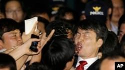 2013年9月5日,韩国左派国会议员李石基(右)在首尔被逮捕后在警察和记者簇拥下高声喊叫。