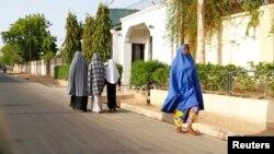 Wasu mata na wucewa a wata unguwa cikin Maiduguri, inda ake aiki da dokar ta baci, Lahadi 19 Mayu, 2013