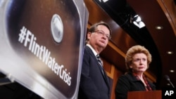FILE - Sen. Gary Peters, D-Mich., left, and Sen. Debbie Stabenow, D-Mich., listen to a question as they discuss proposed legislation to help Flint, Michigan, with its current water crisis during a news conference on Capitol Hill in Washington, Jan. 28, 2016.