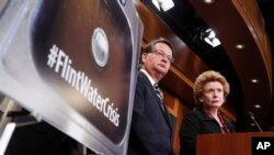 FILE - Sen. Gary Peters, D-Mich., left, and Sen. Debbie Stabenow, D-Mich., discuss proposed legislation to help Flint, Michigan, with its current water crisis during a news conference on Capitol Hill in Washington, Jan. 28, 2016