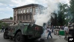 Cư dân địa phương vây quanh một chiếc xe quân sự bị đốt cháy tại hiện trường một vụ giao tranh giữa quân đội Ukraine và những chiến binh thân Nga ở Mariupol, 13/6/2014.