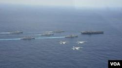 """4月28日在沖繩附近海域,日本兩艘軍艦和兩架F15戰機參加美國核航母""""卡爾·文森""""號為首的美軍戰艦群和航母搭載機聯合軍演時的布陣航行、飛行環節(日本航空自衛隊提供)"""