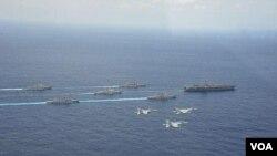 """4月28日在冲绳附近海域,日本两艘军舰和两架F15战机参加美国核航母""""卡尔·文森""""号为首的美军战舰群和航母搭载机联合军演时的布阵航行、飞行环节(日本航空自卫队提供)"""