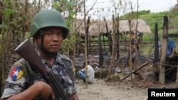 រូបឯកសារ៖ ទាយានយាមព្រំដែនមីយ៉ាន់ម៉ាម្នាក់ឈរយាមនៅពីមុខផ្ទះដែលឆាបឆេះនៅក្នុងការប៉ះទង្គិចរវាងក្រុមយុទ្ធជន និងកងកម្លាំងសន្តិសុខនៅក្នុងភូមិ Tin May រដ្ឋ Rakhine ប្រទេសមីយ៉ាន់ម៉ា កាលពីថ្ងៃទី១៤ ខែកក្កដា ឆ្នាំ២០១៧។