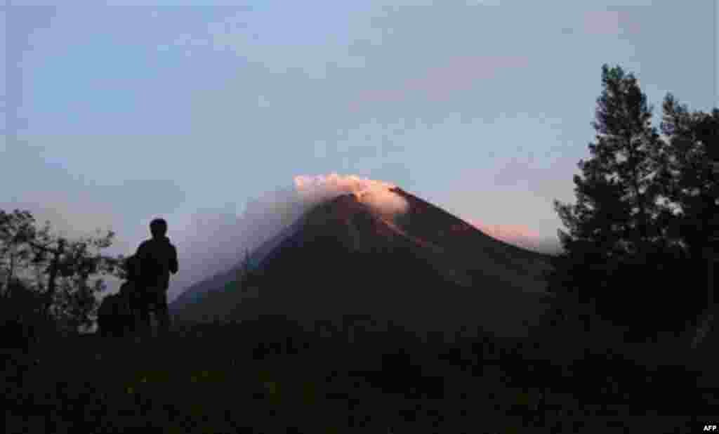 A villager watches Mount Merapi in Kaliadem, Yogyakarta, Indonesia, Tuesday, Oct. 26, 2010. Indonesia's most volatile volcano started erupting Tuesday, after scientists warned that pressure building beneath its dome could trigger the most powerful eruptio