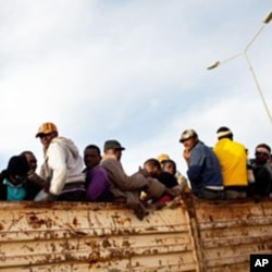 Migrant refugees atop a truck in the Libyan city of Misrata. IOM says it has evacuated some 8,500 migrants from Misrata so far, the majority during the height of the violence there.