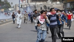 Para demonstran berlarian setelah polisi Pakistan melemparkan gas air mata dalam unjuk rasa yang berakhir dengan kekerasan di dekat gedung konsulat AS di Karachi, Pakistan (17/9).