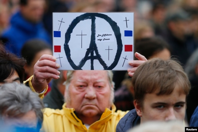 People observe a minute of silence in tribute to victims of Friday's attacks in Paris in front of French embassy, near the Brandenburg Gate in Berlin, Germany, Nov. 16, 2015.
