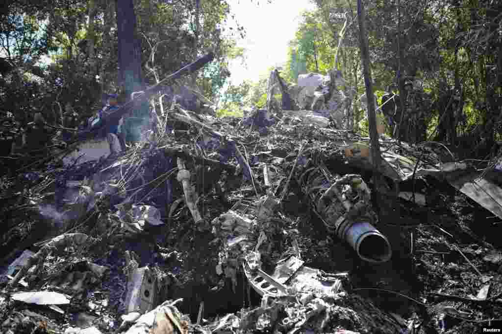 Rescue workers search an air force plane crash site near Nadee village, Xiang Khouang province, Laos, May 17, 2014.