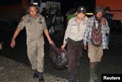 Anggota kepolisian mengevakuasi warga setelah baku tembak antara pasukan keamanan dan kelompok separatis di Mimika, Papua, 8 Maret 2020. (Foto: Sevianto Pakiding/Antara via Reuters)