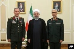 In this photo released by an official website of the office of the Iranian Presidency, President Hassan Rouhani, center, poses for a photo with Turkey's Chief of Staff Gen. Hulusi Akar, left, and Chief of Staff of Iran's Armed Forces, Gen. Mohammad Hossein Bagheri, during their meeting in Tehran, Oct. 2, 2017.