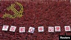 """中国浙江省金华市的中共党员手举""""不忘初心牢记使命""""的标语牌组成中共党旗图案的阵仗。(2019年6月28日)"""