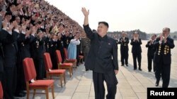 Lãnh đạo Bắc Triều Tiên Kim Jong-Un vẫy chào khi ông đến chụp ảnh với các giới chức, nghệ sĩ, và nhân viên của 1 studio ở Bình Nhưỡng, 19/4/2012
