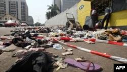 Warga berdiri di dekat pakaian dan barang-barang yang berserakan di jalanan sekitar stadion di kota Abidjan, Pantai Gading (1/1). Sedikitnya 60 orang dilaporkan tewas terinjak-injak saat berdesakan menyaksikan pertunjukan kembang api dalam perayaan Tahun Baru 2013 di sebuah stadion kota ini.