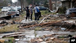 People walk amongst debris from destroyed homes after a tornado tore through the eastern neighborhood in New Orleans, Feb. 7, 2017.
