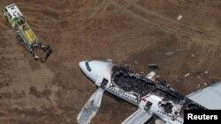 在旧金山国际机场,救援人员站在失事的韩亚航波音777客机附近。(2013年7月6日)