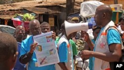 Para petugas kesehatan mengajarkan warga tentang virus Ebola dan bagaimana mencegah infeksi, di Conakry, Guinea. (AP/Youssouf Bah)