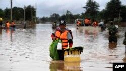ອາສາສະໝັກຄົນນຶ່ງລຸຍນໍ້າຜ່ານຖະໜົນທີ່ຖືກນໍ້າຖ້ວມໃນເມືອງ ສະໜາມໄຊ, ແຂວງ ອັດຕະປື, 26 ກໍລະກົດ. / AFP PHOTO / NHAC NGUYEN