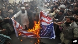 Supporters of religious parties burn a U.S flag during a protest against detained U.S. citizen Raymond Davis in Lahore, February 18, 2011.