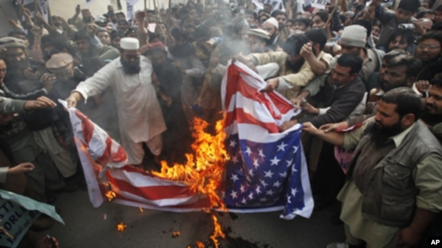Supporters of religious parties burn a U.S flag during a protest against U.S. citizen Raymond Davis near the U.S consulate in Lahore February 18, 2011.