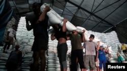 Pekerja di Sidoarjo, Jawa Timur, mengangkut karung-karung berisi gula putih dari gudang ke truk untuk didistribusikan. (Reuters/Sigit Pamungkas)