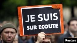 Seorang pengunjuk rasa di Paris mengangkat kertas protes menentang RUU pengawasan luas terhadap pelaku teror, sehari sebelum pemungutan suara di parlemen Perancis (4/5).
